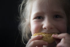 Muchacha que come un buñuelo Fotos de archivo