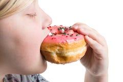 Muchacha que come un buñuelo rosado Imagen de archivo