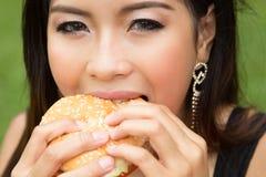 Muchacha que come un cheeseburger Imágenes de archivo libres de regalías