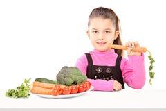 Muchacha que come un manojo de verduras asentadas en la tabla Imagen de archivo libre de regalías