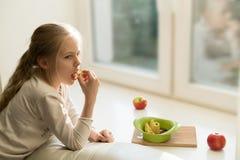 Muchacha que come una manzana al lado de una ventana grande Imagenes de archivo