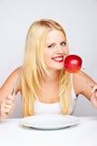 Muchacha que come una manzana roja con una fork Foto de archivo libre de regalías