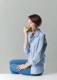 Muchacha que come una manzana verde Imagenes de archivo