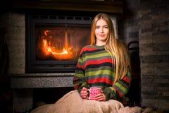 Muchacha que come una taza de té por la chimenea fotos de archivo