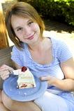 Muchacha que come una torta Fotos de archivo libres de regalías