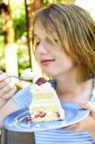 Muchacha que come una torta Imagen de archivo libre de regalías