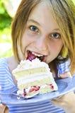 Muchacha que come una torta Imagen de archivo