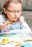 Muchacha que come y que lee fotografía de archivo libre de regalías