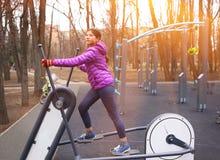 Muchacha que completa un ciclo en el parque de la ciudad en instructor del ciclo del ourdoor Foto de archivo