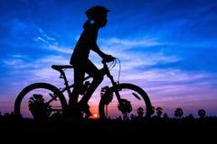 Muchacha que completa un ciclo en el tiempo del crepúsculo de la montaña Fotos de archivo