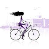 Muchacha que completa un ciclo en la ciudad Foto de archivo