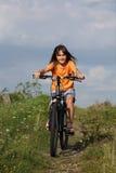 Muchacha que completa un ciclo en paisaje rural Imagenes de archivo