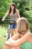 Muchacha que completa un ciclo en parque Imagen de archivo libre de regalías