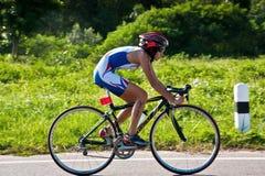 Muchacha que completa un ciclo en triatlon fotos de archivo