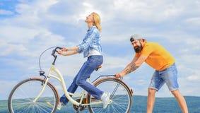 Muchacha que completa un ciclo mientras que el novio la apoya Enseñe al adulto a montar la bici Las ayudas del hombre mantienen e fotos de archivo libres de regalías
