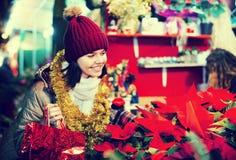 Muchacha que compra composiciones florales en el mercado de la Navidad Fotografía de archivo libre de regalías