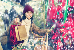 Muchacha que compra composiciones florales en el mercado de la Navidad Imagen de archivo libre de regalías