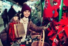 Muchacha que compra composiciones florales en el mercado de la Navidad Fotos de archivo libres de regalías
