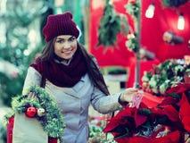 Muchacha que compra composiciones florales en la feria de la Navidad Foto de archivo