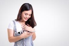 Muchacha que comprueba el teléfono con la alegría, copia-espacio aislado Imagenes de archivo