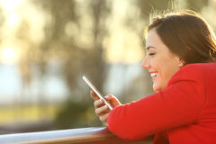 Muchacha que comprueba el teléfono elegante al aire libre en invierno Foto de archivo