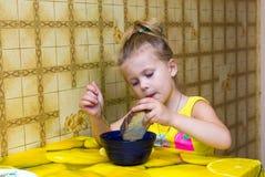 muchacha que concentra clavada el pan en una taza Fotos de archivo
