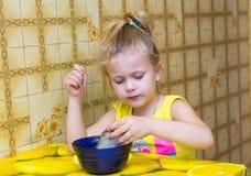muchacha que concentra clavada el pan en una taza Fotos de archivo libres de regalías
