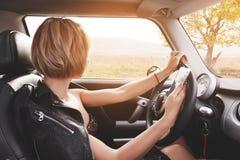 Muchacha que conduce un texto que mecanografía del coche en el teléfono y que mira hacia fuera la ventana Fotos de archivo