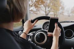 Muchacha que conduce un texto que mecanografía del coche en el teléfono y que mira hacia fuera la ventana Imagen de archivo libre de regalías