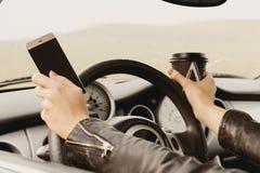 Muchacha que conduce un texto que mecanografía del coche en el teléfono y que mira hacia fuera la ventana Imágenes de archivo libres de regalías
