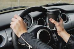 Muchacha que conduce un texto que mecanografía del coche en el teléfono y que mira hacia fuera la ventana Fotografía de archivo libre de regalías