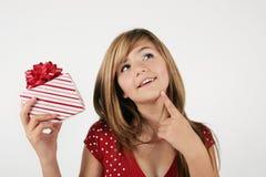Muchacha que conjetura sobre presente Foto de archivo libre de regalías