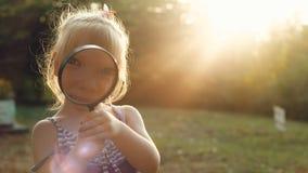 Muchacha que considera a través de una lupa la puesta del sol almacen de video
