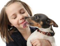 Muchacha que consigue besos de perro Imágenes de archivo libres de regalías
