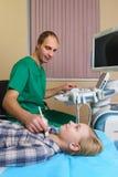 Muchacha que consigue ultrasonido de una tiroides de doctor Foto de archivo libre de regalías