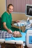 Muchacha que consigue ultrasonido de una tiroides de doctor Fotografía de archivo libre de regalías