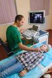 Muchacha que consigue ultrasonido de una tiroides de doctor Imagen de archivo libre de regalías
