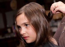 Muchacha que consigue un corte de pelo Foto de archivo libre de regalías
