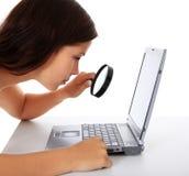 Muchacha que controla la computadora portátil con la lupa Fotografía de archivo libre de regalías