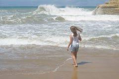 Muchacha que corre cerca del mar con las ondas Foto de archivo libre de regalías