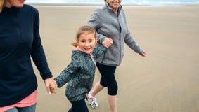 Muchacha que corre con dos mujeres en la playa Fotografía de archivo