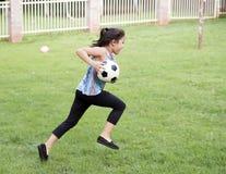 Muchacha que corre con el balón de fútbol Imágenes de archivo libres de regalías