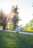 Muchacha que corre con la cometa del arco iris Raza mixta - africano y caucásico Día de verano en parque Fotos de archivo libres de regalías