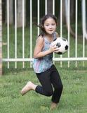 Muchacha que corre con un balón de fútbol Foto de archivo