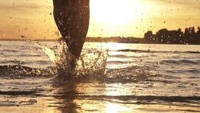 Muchacha que corre en agua poco profunda en la puesta del sol Cámara lenta metrajes