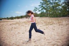 Muchacha que corre en arena de la isla de Olkhon Foto de archivo