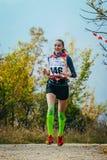 Muchacha que corre en el camino en bosque del otoño en calcetines de la compresión y la cinta del kinesio en rodillas Imágenes de archivo libres de regalías