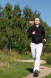 Muchacha que corre en el parque. Tiro ancho Fotografía de archivo
