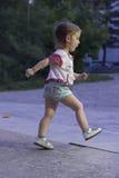 Muchacha que corre en la calle del parque Imagen de archivo
