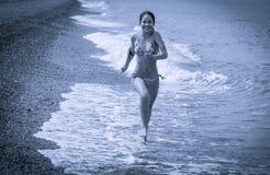 Muchacha que corre en la costa con los guijarros, imagen entonada azul Fotos de archivo